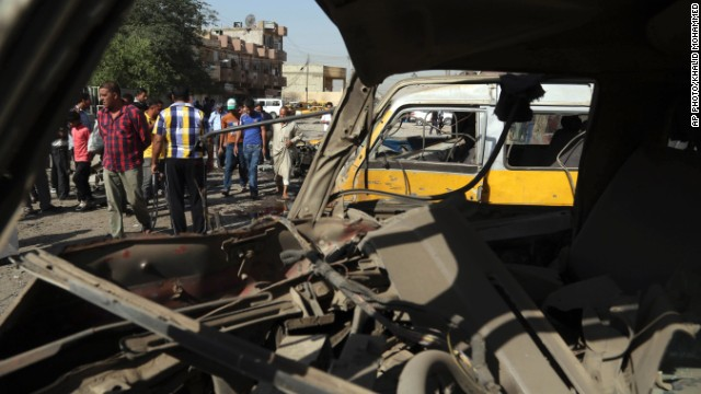 Citizens are seen through a broken window of a bus destroyed in a blast at a bus station in Baghdad Sunday.