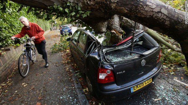 A car in London is crushed by a fallen tree on Monday.