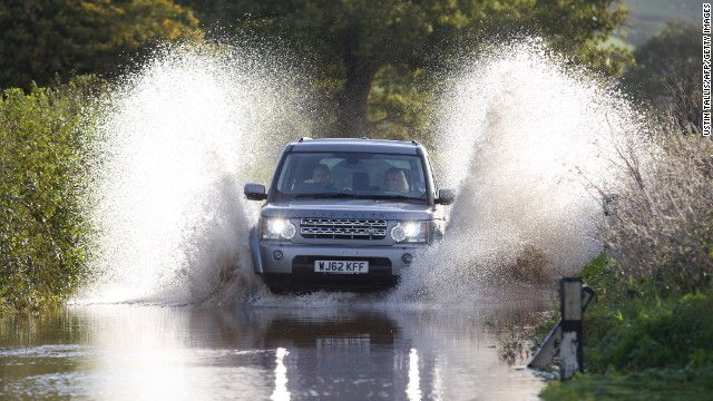 A vehicle splashes through a flooded section of road near the English village of Whitford on Monday.