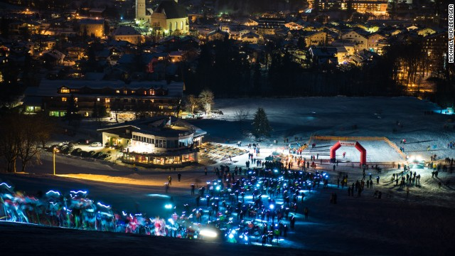 Competitors in their hundreds set off in a mass start for the Streif Vertical Up from Kitzbuhel, lighting up the snow with their head torches as they begin the tortuous climb to the top.