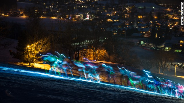 The lights of the competitors are blurred in a photographic trick as they charge up the Streif, with the Austrian resort also lit up below them.