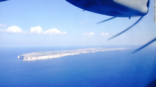 The view out of a window on the Frontex surveillance plane shows the Italian island of Lampedusa. More than 300 migrants died in a shipwreck while attempting to reach the island in early October.