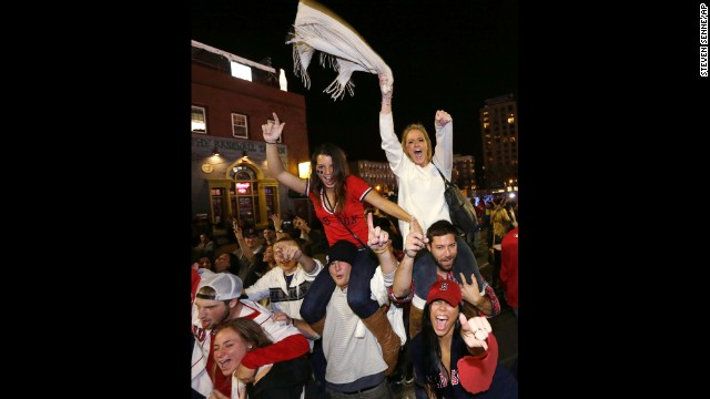 Fans celebrate on the street near Fenway Park.