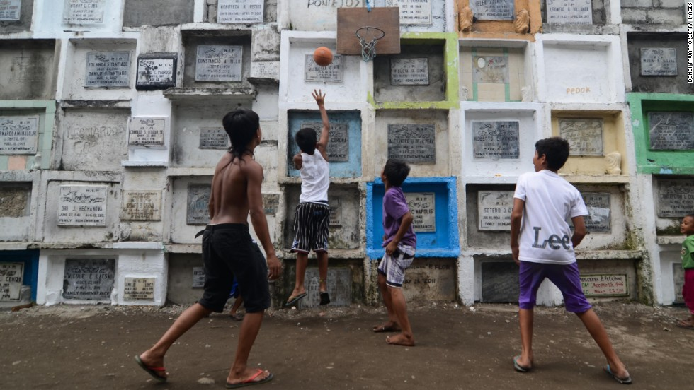 OCTOBER 31 - MANILA, PHILIPPINES: Youngsters play basketball at a cemetery, marking one of the most important holidays for the largest Catholic nation in Asia, <a href='http://edition.cnn.com/SPECIALS/cnn-celebrates'>All Saints' Day</a>. Filipinos traditionally visit cemeteries to hold vigils and large family reunions, but the atmosphere is far from sad, as the usually silent graveyards turn into parties with food and music.