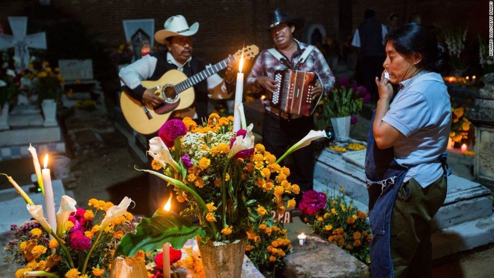A Mexican woman wipes away a tear as a Mariachi band plays at the tomb of a loved one during the Dia de los Muertos, or Day of the Dead, festival in Oaxaca, Mexico, on Thursday, October 31. Celebrated in Mexico and around the world, the traditional holiday honors the lives of lost family members and friends.
