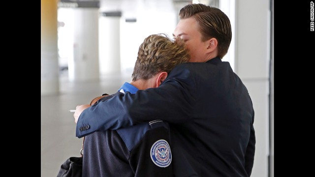 Transportation Security Administration employees hug outside Terminal 1.