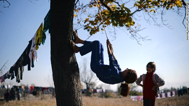 A Syrian refugee uses a rope to climb a tree at the Vrazhdebna shelter Tuesday, October 29.