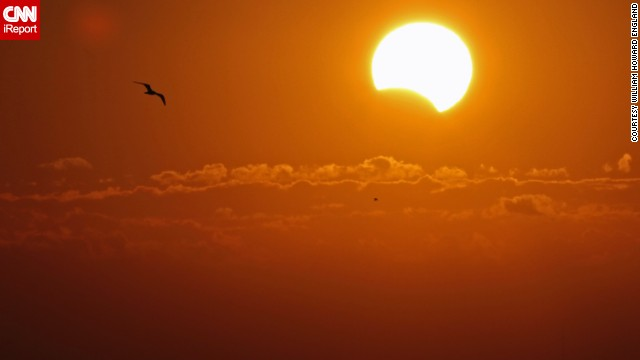<a href='http://ireport.cnn.com/docs/DOC-1055901'>William England</a> could not see the eclipse with his naked eye while out in Titusville, Florida. But he took photos of the sunrise anyway. Only later did he realize he captured the solar event through his camera.