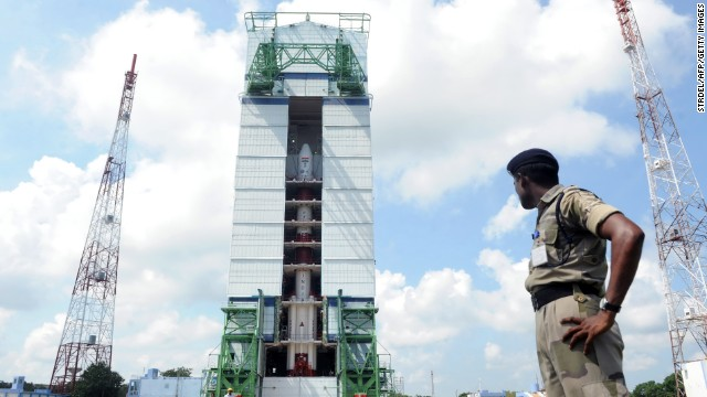 An Indian security forces member watches the PSLV-C25 launch vehicle carrying the Mars Orbiter probe as its payload on October 30, 2013.