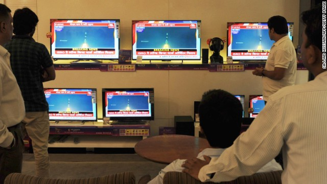 Indian bystanders watch a bank of screens showing the live telecast of the launch of India's Mars Orbiter Mission inside a showroom in New Delhi on November 5, 2013.