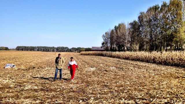Former Masanjia inmate Liu Hua (right) walks across the field outside the female inmates' quarters and talks to a CNN reporter.