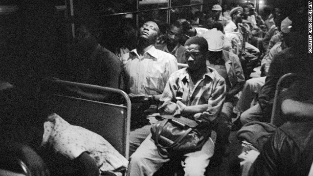 "South Africa, 1983: Exhausted workers cram onto a ""blacks only"" bus traveling from a segregated homeland into Pretoria at two o'clock in the morning. The image is the work of South African photographer David Goldblatt."