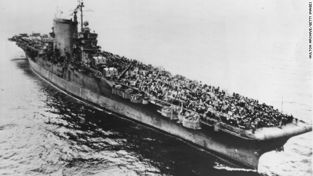 Crew members of the USS Saratoga, named after the Revolutionary War battle, cover the deck as the ship moves toward the Golden Gate Bridge in San Francisco in 1945. The ship was one of two members in the Lexington class of aircraft carriers.