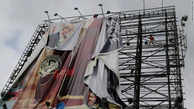 Workers bring down a billboard in Makati, Philippines, on November 7 before Haiyan makes landfall.