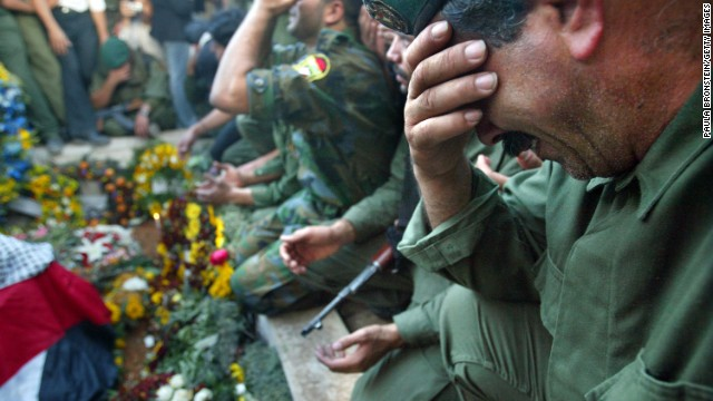 Palestinian security forces cry over Arafat's grave after he was buried at his compound in Ramallah on November 12, 2004.