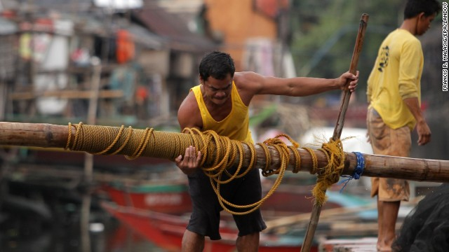 A fisherman lifts a post to reinforce his home at a coastal village in Las Pinas on November 8.