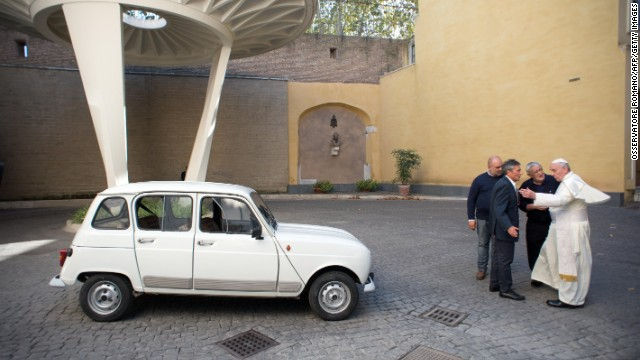 Francis has eschewed fancy cars. Here, Father Don Renzo Zocca, second from right, offers his white Renault 4L to the Pope during a meeting September 7 at the Vatican.