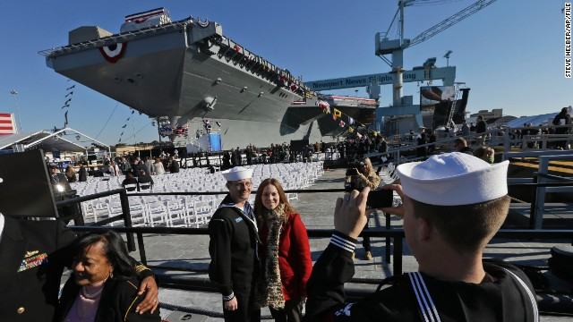 U.S. Navy Boatswain's Mate Ben Hansen and his wife Jessica are photographed in front of the Navy's newest nuclear-powered aircraft carrier, the USS Gerald R. Ford, during the christening of the ship at Newport News Shipbuilding in Newport News, Virginia. The late president's daughter, Susan Ford Bales, christened the ship.