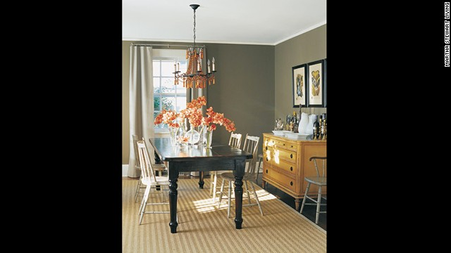 Dark stain on the table, painted chairs and an antique sideboard stand out against gray walls.