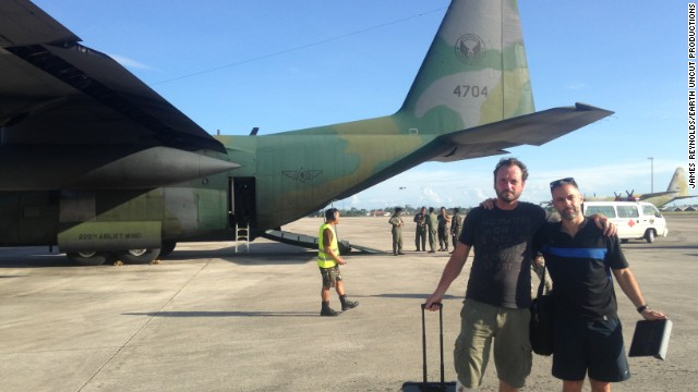 Relieved storm chasers Mark Thomas and Josh Morgerman near the C-310 they caught out of Tacloban after hearing a tip-off about military flights out of the typhoon-hit Filipino city.