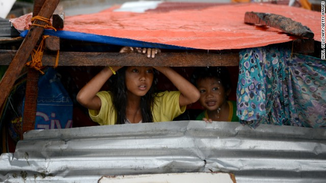 Children peek out from their makeshift shelter in Tacloban on Sunday, November 10.