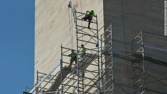 Workers walk on scaffolding around the monument as repairs continue in April.