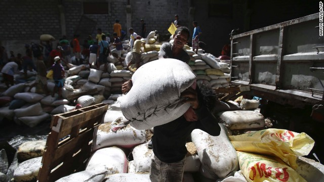 Residents carry bags of rice from a Tacloban warehouse that they stormed November 11 because of a food shortage.