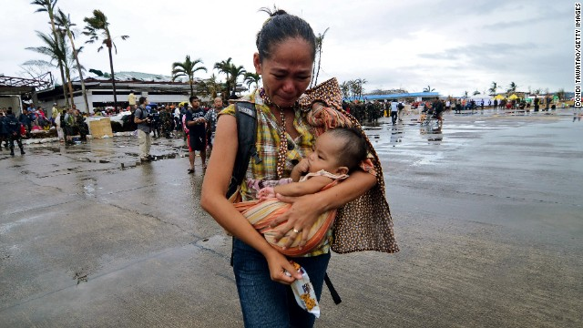 A woman weeps as she carries a child to a military aircraft in Leyte on November 12.