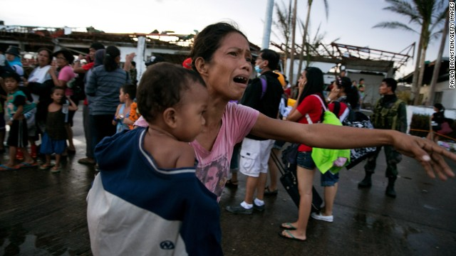 A woman cries November 12 as other survivors wait to evacuate Tacloban.