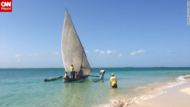 A traditional wooden sailboat, called a dhow, makes its way into the crystal waters of Zanzibar's Menai Bay.