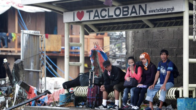 People wait at a bus stop November 12 in Tacloban.