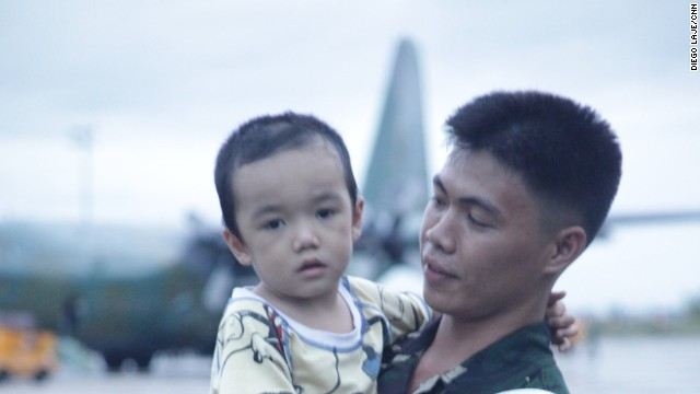 A child is comforted by a soldier after being rescued and brought to Mactan Air Base.