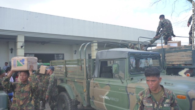 Trucks loaded with relief supplies line up along the road that connects the Mactan air base to the runway at Cebu International Airport.