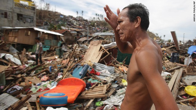 A man looks at his home destroyed by Typhoon Hayian in Tacloban, Philippines, on Wednesday, November, 13. Haiyan, one of the strongest storms in recorded history, decimated parts of the Philippines. President Benigno Aquino III said the typhoon may have killed as many as 2,500 people.