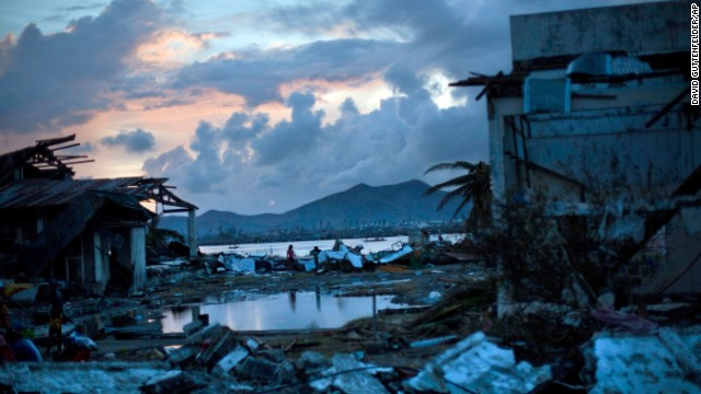 Survivors walk through the ruins of their neighborhood outside Tacloban on November 13.