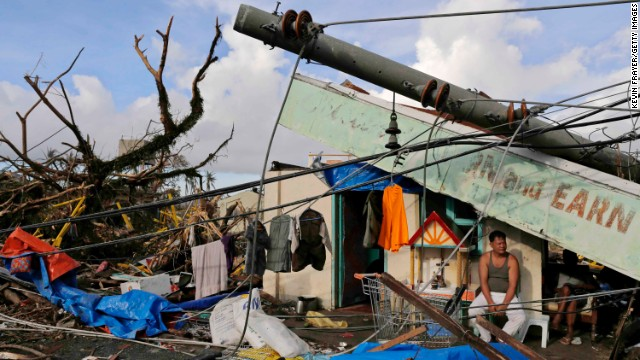 A man sits in front of his destroyed business in Tacloban on November 13.