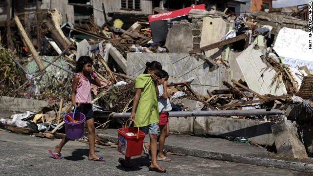Children carry relief goods as they pass by damaged houses in Tacloban on November 13.