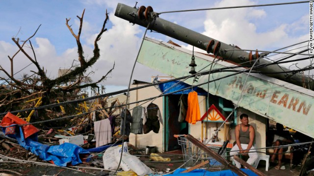 A man sits in front of his destroyed business November 13 in Tacloban.