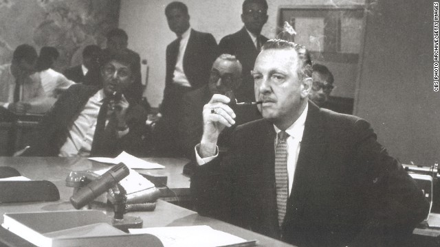 "Walter Cronkite sits behind the news desk on the set of the ""CBS Evening News with Walter Cronkite"" in August 1963. One month later, it became network television's first nightly half-hour news program."