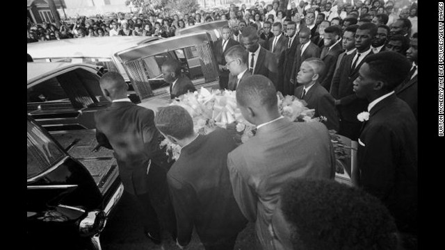 A coffin is loaded into a hearse at a funeral in Birmingham, Alabama, for victims of the 16th Street Baptist Church bombing. Four African-American girls were killed and at least 14 others were wounded when a bomb blast tore through church services on September 15, 1963. Three former Ku Klux Klan members were later convicted of murder for the bombing.