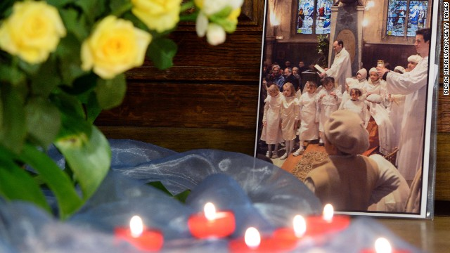 Candles and flowers sit next to a photo of kidnapped priest Georges Vandenbeusch during a Thursday vigil south of Paris.