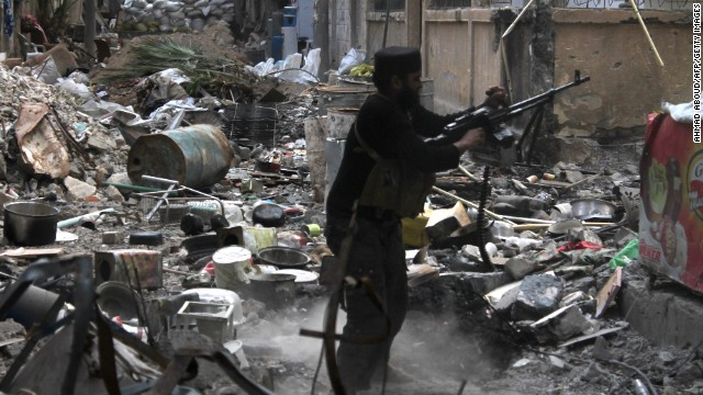 A rebel fighter fires his weapon as he stands amid rubble and debris during clashes with Syrian government forces in Deir Ezzor, Syria, on Monday, November 11.