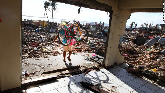 A man carries a bicycle as he walks through the ruins of a Tacloban building November 16.
