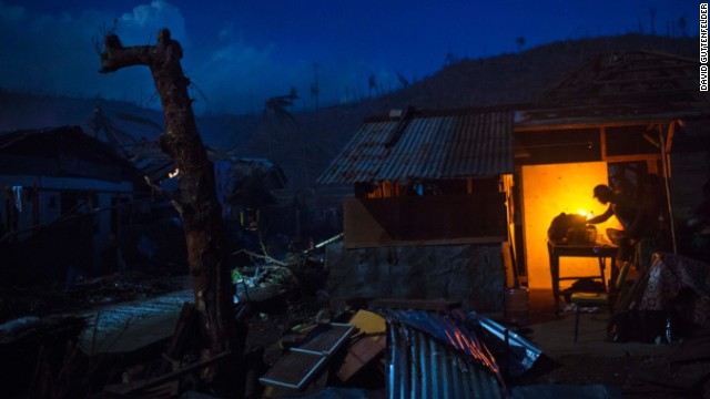 A survivor cooks dinner in front of his damaged home in Marabut, Philippines, on Friday, November 15.