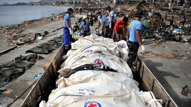 Corpses are collected and loaded on trucks to be taken to mass graves in Tacloban on November 16.