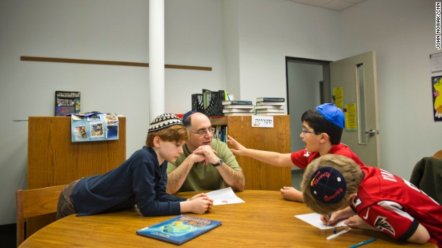 James Weinberg helps his 9-year-old son, Reese, second from right, and fellow fourth-graders work on geography lessons at Congregation Or Hadash in Sandy Springs, Georgia.