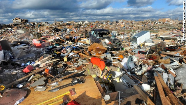 A firefighter, in lower center of photo, peers down into the home of a colleague whose home was destroyed when a tornado swept through Washington, Illinois, on November 17.
