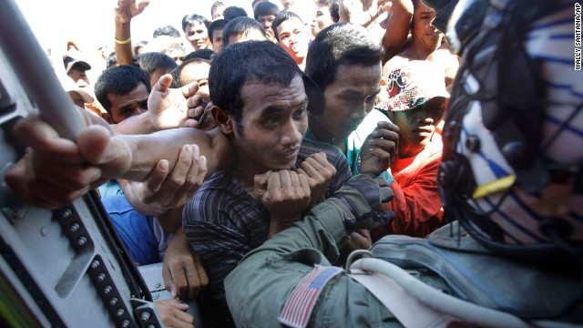 People are held back as the U.S. Navy delivers aid from a helicopter in San Jose, Philippines, on November 18.