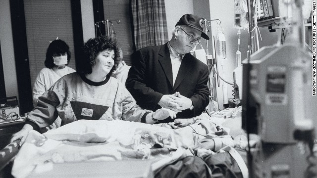John stands by the bed of AIDS patient Ryan White at a Florida hospital in 1990.