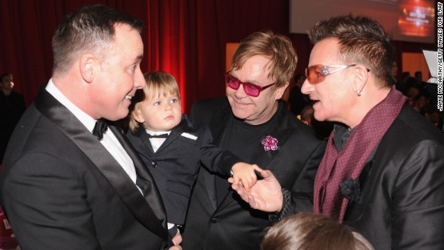 John, partner David Furnish and their son, Zachary, talk with singer Bono, right, at an Academy Awards viewing party in February.